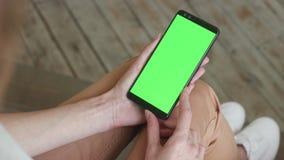 Schermo verde sullo smartphone mobile della giovane donna a casa per la chiave di intensit archivi video