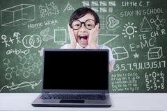Schermo vuoto del computer portatile e piccolo studente nella classe Fotografia Stock