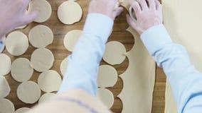 Scherp deeg in cirkels, hoogste mening scène De Bollen van het voorbereidingsvlees Ontwikkel het deeg en snijd cirkels uit het stock footage