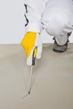Scherp hulpmiddel dat cementvloer controleert Stock Afbeeldingen