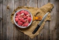 Scherp ruw vlees een groot mes Op houten lijst Ondiepe diepte van gebied Royalty-vrije Stock Foto's
