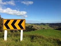 Scherpe bochtverkeersteken in landelijk Nieuw Zeeland Stock Afbeelding