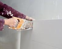 Scherpe de hand vuile zaag van het gipsplaatpleister Stock Foto