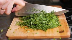 Scherpe dille De vrouwelijke handen snijden dille met een groot mes op een houten scherpe raad stock footage