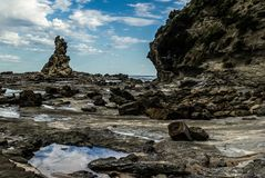 scherpe en ruwe klippenrotsen die uit het water van de Australische kustlijn te voorschijn komen royalty-vrije stock afbeelding