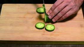 Scherpe komkommer met mes stock videobeelden