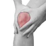 Scherpe pijn in een mensenknie. Mannelijke holdingshand aan vlek van knie-ACH Stock Foto's