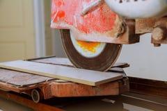 Scherpe porseleintegels die een zaag van het diamantblad gebruiken stock foto