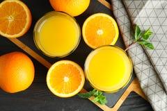 Scherpe raad met jus d'orange, munt en sinaasappelen en keukenhanddoek op houten achtergrond, hoogste mening Verse dranken royalty-vrije stock fotografie