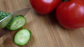 Scherpe verse groene komkommer op een houten raad De kok sneed groenten met een mes Besnoeiingen in de helft stock videobeelden