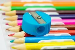 Scherper op kleurrijke pPencilslijper op kleurrijke potlodenachtergrond School stationeencils achtergrond De kantoorbehoeften van Royalty-vrije Stock Foto's