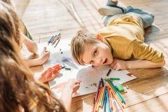 Scherza attingere la carta con le matite mentre si trovano sul pavimento Immagine Stock
