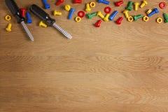 Scherza gli strumenti dei giocattoli della costruzione: cacciaviti variopinti, viti e dadi su fondo di legno Vista superiore Disp Immagini Stock