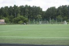 Scherza i giocatori dei bambini piccoli di calcio di calcio una partita sul campo di football americano, Russia Berezniki 25 lugl fotografie stock