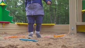 Scherza i giochi Neonato che scava nella sabbiera Sorrisi e tocchi la sabbia stock footage