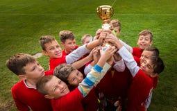 Scherza il calcio di calcio - giocatori dei bambini che celebrano con un trop Fotografia Stock