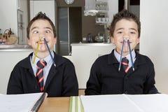 Scherza il gioco mentre fanno il compito a casa Immagini Stock