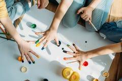 Scherza la pittura sulla carta con le mani mentre si siedono sul pavimento Fotografia Stock