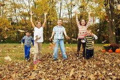 Scherza le foglie di autunno di lancio nell'aria fotografia stock libera da diritti