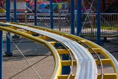 Scherza le rotaie gialle delle montagne russe in parco di divertimenti fotografie stock