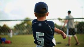 Scherzen Sie auf seiner Baseballuniform, die hinter Zaun vor Baseballpraxis ausdehnt stock video footage