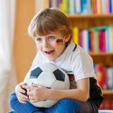 Scherzen Sie aufpassenden Fußball oder Fußballspiel des Jungen im Fernsehen Stockbild