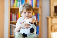 Scherzen Sie aufpassenden Fußball oder Fußballspiel des Jungen im Fernsehen Lizenzfreies Stockbild