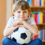 Scherzen Sie aufpassenden Fußball oder Fußballspiel des Jungen im Fernsehen Stockfoto