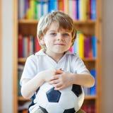 Scherzen Sie aufpassenden Fußball oder Fußballspiel des Jungen im Fernsehen Stockfotos