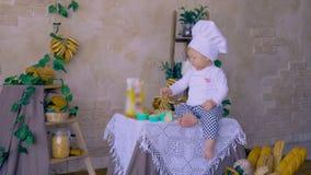 Scherzen Sie, Baby in der Kochkappe, die mit Teig spielt stock footage