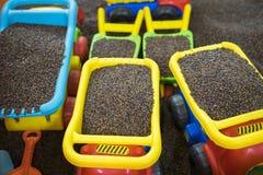 Scherzen Sie bunte Spielwaren mit Mann gemachtem sicherem Sand von Kassie tora Samen Stockfotografie