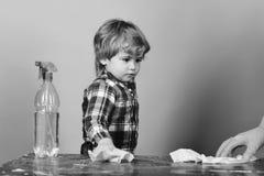 Scherzen Sie das Abwischen der Tabelle durch Lappen nahe Reinigungsspray Junge im karierten Hemd auf blauem Hintergrund Kleines H Stockfoto