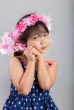 Scherzen Sie das Halten der Blume auf dem Grau/Kind, welche die Blume/Kind Blume, Atelieraufnahme halten hält Stockfoto