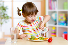 Scherzen Sie das Mädchen, das gesundes Gemüse im Kindergarten oder in der Kindertagesstätte isst stockfotos