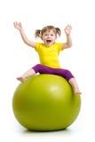 Scherzen Sie das Mädchen, das Gymnastik mit dem Ball tut, der auf weißem Hintergrund lokalisiert wird Stockbild