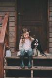 Scherzen Sie das Mädchen, das mit ihrem Spanielhund spielt und auf Treppe am hölzernen Blockhaus sitzen Lizenzfreie Stockbilder
