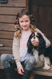 Scherzen Sie das Mädchen, das mit ihrem Spanielhund spielt und auf Treppe am hölzernen Blockhaus sitzen Stockbilder
