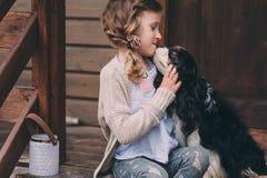 Scherzen Sie das Mädchen, das mit ihrem Spanielhund spielt und auf Treppe am hölzernen Blockhaus sitzen Stockfotografie