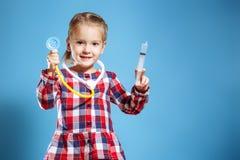 Scherzen Sie das Mädchen, das Doktor mit Spritze und Stethoskop auf einem blauen Hintergrund spielt stockfotografie