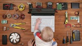 Scherzen Sie das Sitzen mit seinem Vater für die Arbeitsplatzcomputerreparatur und drücken Sie die Tasten auf einem Laptop Hölzer stock video