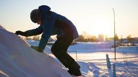 Scherzen Sie das Spielen, in den schneebedeckten Bergen, zum zur Spitze zu klettern Am Sonnenuntergang stock video