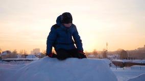 Scherzen Sie das Spielen, in den schneebedeckten Bergen, zum zur Spitze zu klettern Am Sonnenuntergang stock footage