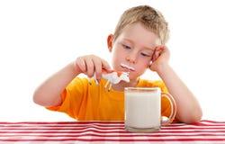 Scherzen Sie das Spielen mit Spielzeugkuh hinter Glas Milch lizenzfreie stockfotografie