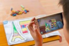 Scherzen Sie das Spielen von vergrößerten Popup- Malereien der Wirklichkeit des gefüllten Triumphbogens u. des Eiffelturms über M lizenzfreies stockfoto