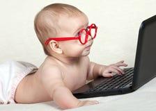 Scherzen Sie in den Gläsern, welche die Laptopanzeige betrachten Stockbild