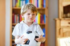 Scherzen Sie den Jungen, der über verlorenes Fußball- oder Fußballspiel traurig ist Stockfotos
