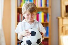 Scherzen Sie den Jungen, der über verlorenes Fußball- oder Fußballspiel traurig ist Lizenzfreie Stockbilder