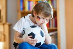 Scherzen Sie den Jungen, der über verlorenes Fußball- oder Fußballspiel traurig ist Stockbild