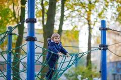 Scherzen Sie den Jungen, der auf Spielplatz im Freien am Herbsttag klettert Lizenzfreie Stockbilder