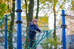 Scherzen Sie den Jungen, der auf Spielplatz im Freien am Herbsttag klettert Stockfoto